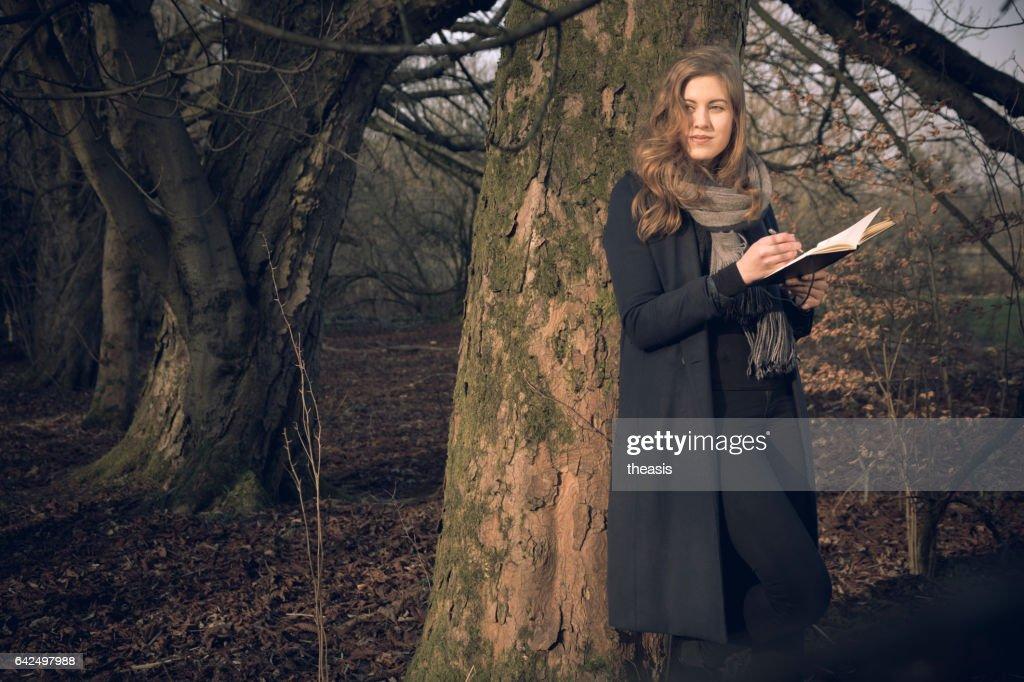 Atractiva mujer joven escribiendo en su diario : Foto de stock