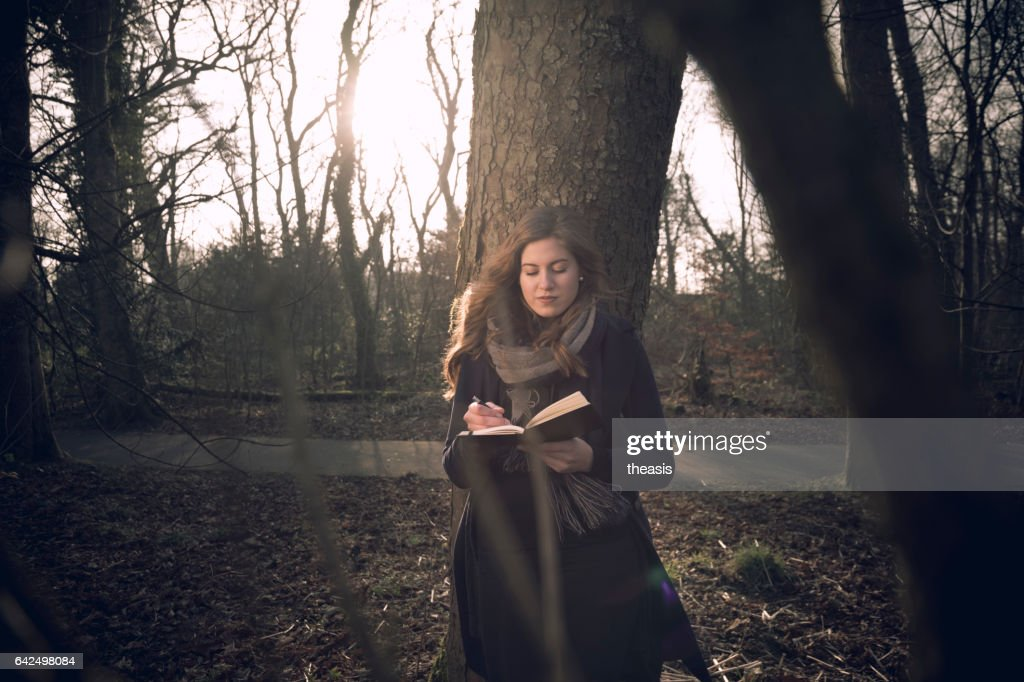 Attractive young woman writing in her journal : Stock Photo