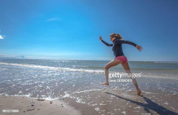 attractive young women running on the beach, pas de calais, bitch., pas de calais, bitch. - female anatomy stock photos and pictures