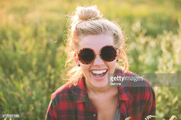 Attractive Youth Female Laughing with Sunglasses on.
