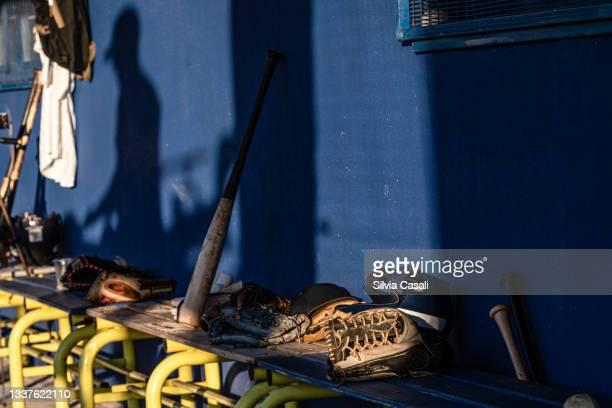 attrezzatura da baseball sulla panchina del dugout - silvia casali stock pictures, royalty-free photos & images