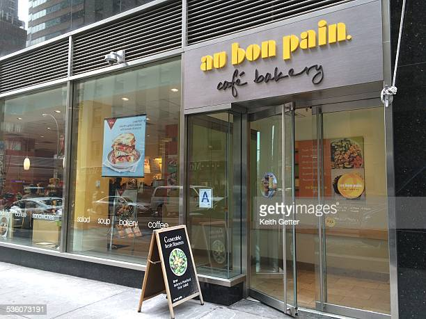 Au Bon Pain glass storefront reflects city activity in lower Manhattan NYC near the Financial District