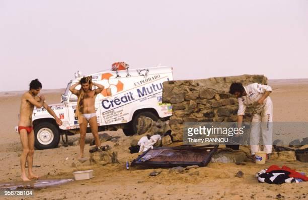 Au petit matin des concurrents du rallye ParisDakar font leur toilette lors de la traversée du désert du Ténéré le 12 janvier 1984 Algérie