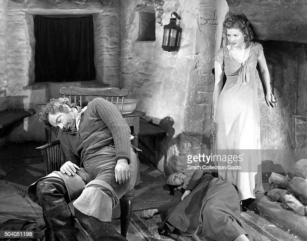 Au Royaume Des Cieux movie still depicting a women approaching two sleeping men from the film noir movie by director Julien Duvivier which tells the...