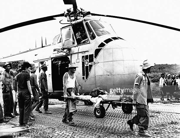 Au sortir de l'hélicoptère un blessé de Diên Biên Phu sur un brancard est porté par deux hommes au Viêt Nam en 1954