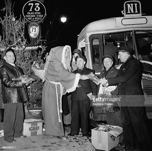 Au terminus des autobus de nuit Avenue Victoria un Père Noël devant un sapin de Noël illuminé remet le colis de charcuterie offert par le Club des...