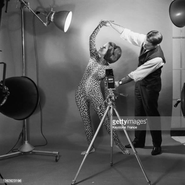 Au travail, Natacha, mannequin, se fait montrer une pose par le photographe, à Paris, France en 1964.