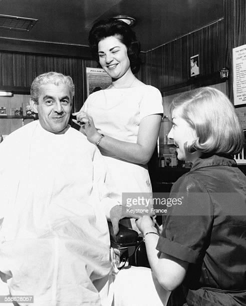 Au Westbury Hotel Ann Hoffman la seule femme barbier rase un client pendant qu'une autre autre jeune femme lui fait la manucre à Londres RoyaumeUni
