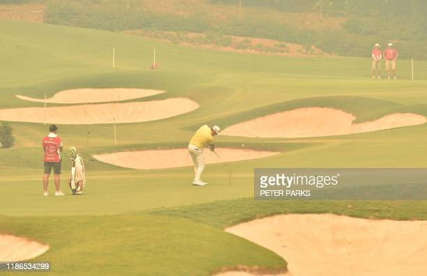 Auatralian golfer Damien Jordan hits a shot on the fairway through thick haze from bushfires at the 1st hole on day one of the Australian Open golf...