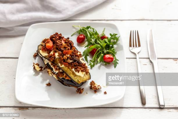 Aubergine lasagne on plate, rucola and tomato, vegetarian