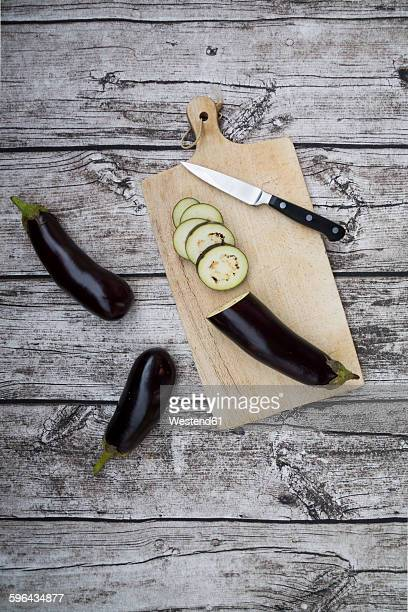 Aubergines on chopping board, knife