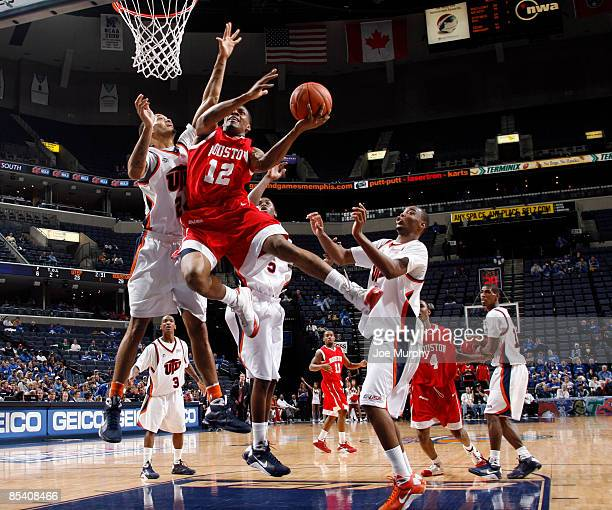 Aubrey Coleman of the Houston Cougars drives to the basket for a layup against Tavaris Watts of the UTEP Miners during the Quarterfinals of the...