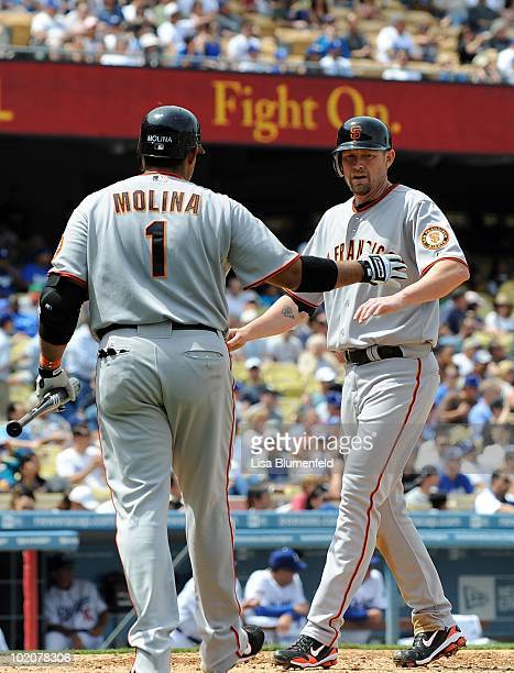 Aubrey Huff celebrates with teammate Bengie Molina of the San Francisco Giants after scoring in the third inning against the Los Angeles Dodgers at...