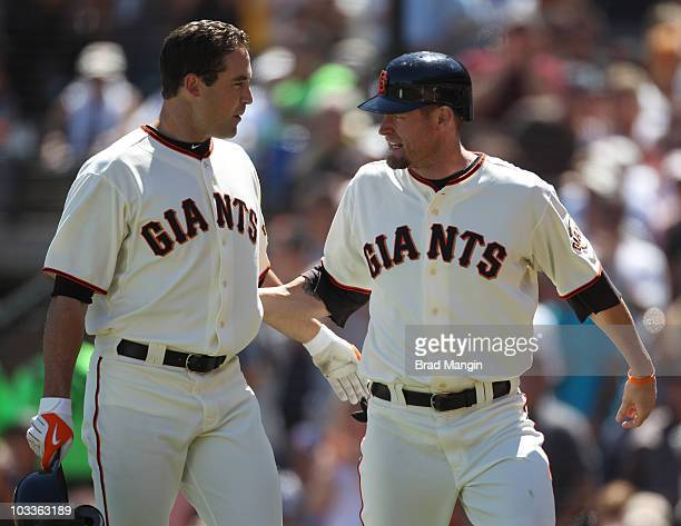 Aubrey Huff of the San Francisco Giants greets teammate Pat Burrell after Burrell hit a grand slam against the Chicago Cubs during the game at ATT...