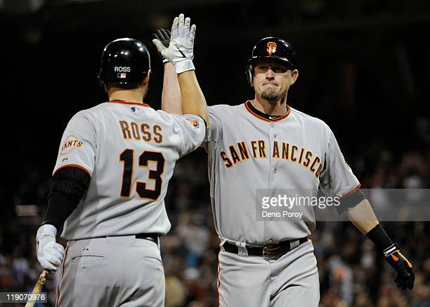 Aubrey Huff of the San Francisco Giants is congratulated by teammate Cody Ross after Huff hit a solo home run during the ninth inning of a baseball...