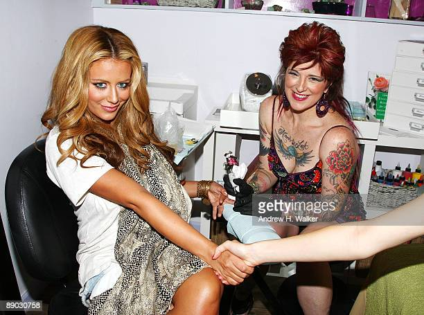 Aubrey O'Day gets a tattoo from tattoo artist Friday Jones during the opening of Friday Jones Fifth Ave Tattoo Studio at Senses NY Salon Spa on July...