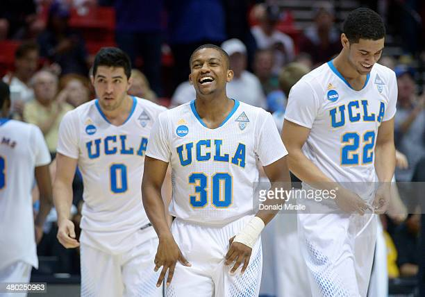 Aubrey Williams Nick Kazemi and Noah Allen of the UCLA Bruins celebrate their 77 to 60 win over the Stephen F Austin Lumberjacks during the third...