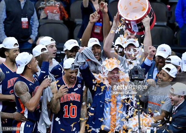 Auburn coach Bruce Pearl covered in confetti celebrates with his Tigers after they took down Kentucky 7771 in overtime in the NCAA Midwest Regional...