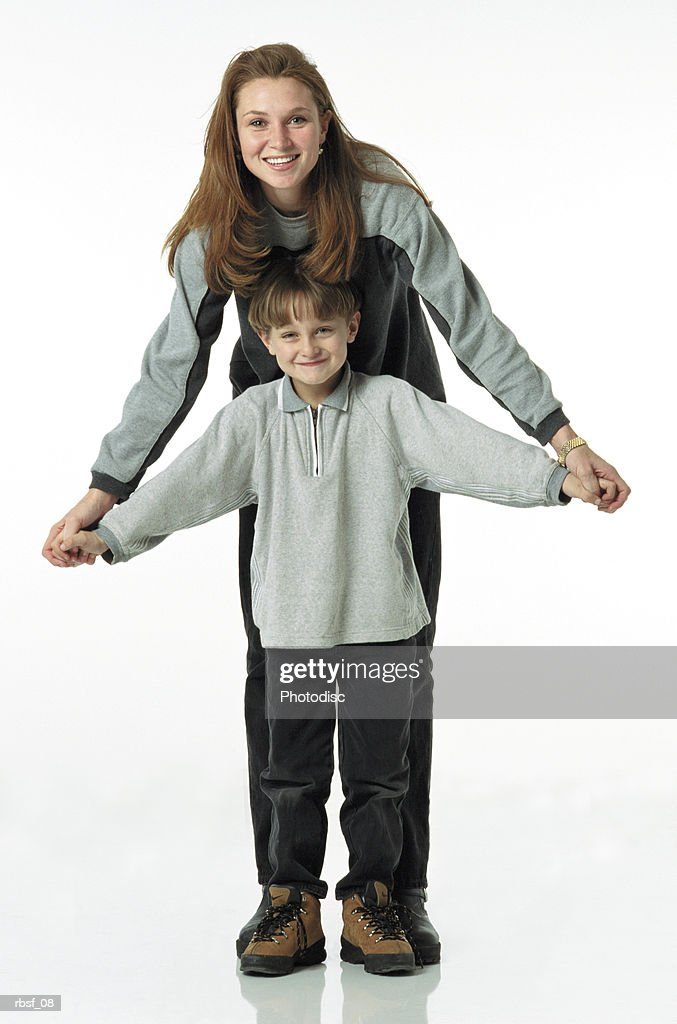 auburn long haired young mother stands behind a child and they hold hands while wearing gray and black clothing : Foto de stock