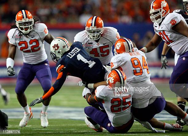 Auburn running back Brad Lester is brought down by Clemson safety Michael Hamlin and Clemson defensive end Phillip Merling during the first quarter...