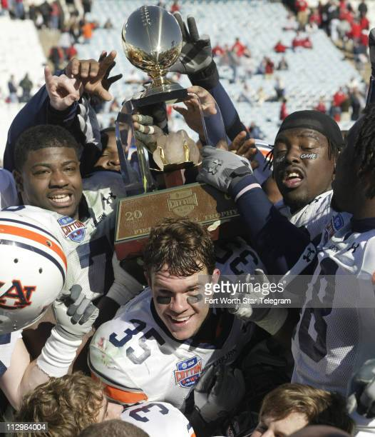 Auburn Tigers players celebrate with the Field Scovell Trophy after defeating the Nebraska Cornhuskers 1714 in the Cotton Bowl Classic in Dallas...