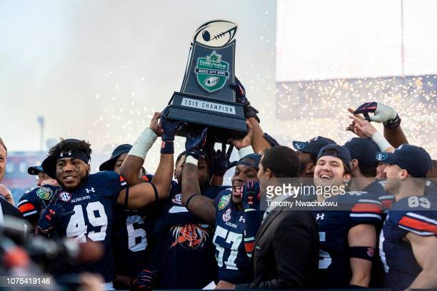 Auburn Tigers players hoist the Franklin American Mortgage Music City Bowl championship trophy after defeating the Purdue Boilermakers at Nissan...