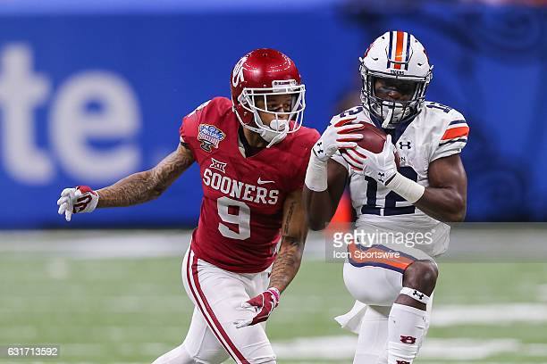 Auburn Tigers wide receiver Eli Stove catches a pass against Oklahoma Sooners linebacker Tay Evans during the game between the Auburn Tigers and the...