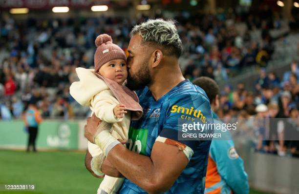Auckland Blues captain Patrick Tuipulotu holds his baby after the Super Rugby Trans Tasman final match against the Highlanders in Auckland on June...