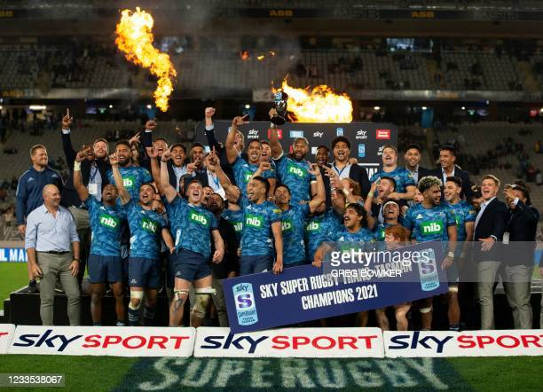 Auckland Blues players celebrate with the Super Rugby Trans Tasman Trophy after winning the rugby final against the Highlanders in Auckland on June...
