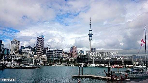 auckland harbor by buildings in city against cloudy sky - waitemata harbor stock photos and pictures