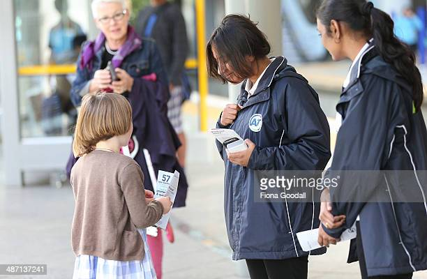Auckland Transport staff hand out electric train information to passengers as they wait for Auckland Transport's new electric trains at Newmarket...