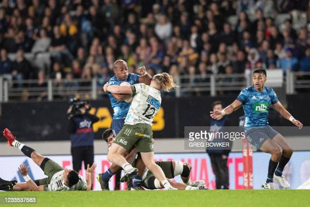 Auckland's Blues Mark Telea is tackled during the Super Rugby Trans-Tasman final match between the Blues and Highlanders in Auckland on June 19, 2021.