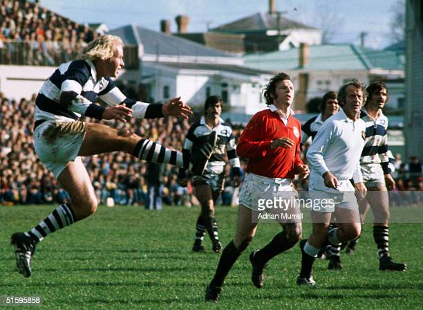 Auckland's Colin Farrell clears the ball as J.J Williams of the British Lions closes in during the match between Auckland and the British Lions on...