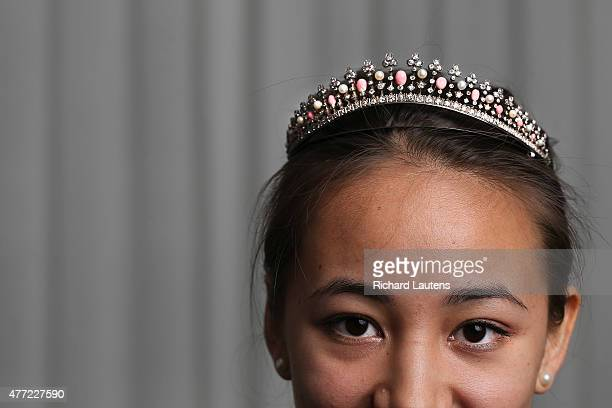 Auction assistant Jade Pauk tries on the signature piece of the auction a tiara made of conch pearls regular pearls and diamonds Preview of Dupuis...