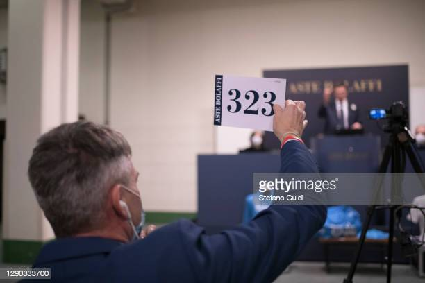 """Auction buyers buy a Diego Armando Maradona shirt by phone during of the """"Sport Memorabilia"""" auction on December 09, 2020 in Turin, Italy. """"Sport..."""