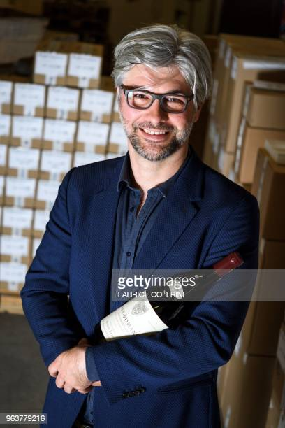 Auction house Baghera Wines executive director Michael Ganne poses on April 27, 2018 in Geneva with a magnum of Vosne-Romanee 1er cru Cros Parantoux...
