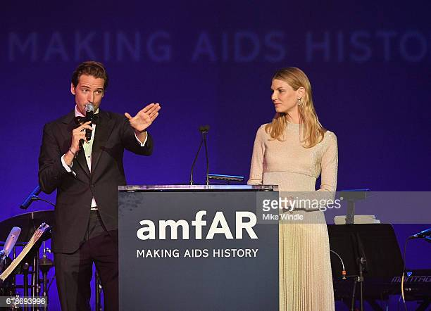 Auctioneer Alexander Gilkes and model Angela Lindvall speak onstage at amfAR's Inspiration Gala Los Angeles at Milk Studios on October 27 2016 in...