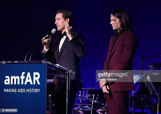 Auctioneer Alexander Gilkes and recording artist Nikolai Haas speak onstage during amfAR's Inspiration Gala Los Angeles at Milk Studios on October 27...