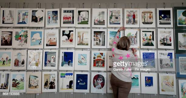 Auctioneer Catherine Southon holds examples from the Smilby cartoon collection, including works that appeared in Playboy, as she sets up her sale...