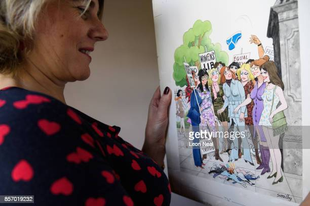 """Auctioneer Catherine Southon poses with one of the hundreds of original works by Playboy cartoonist """"Smilby"""" at a preview of two forthcoming sales of..."""