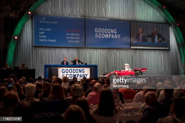 Auctioneer Charles Ross right gestures as David Gooding president and chief executive officer of Gooding and Company listens while auctioning a 1975...