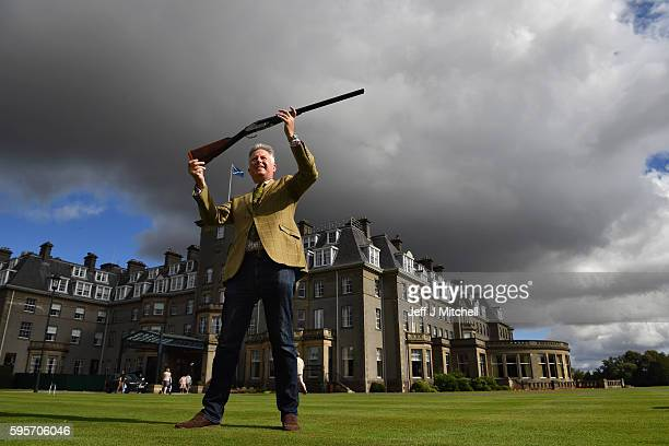 Auctioneer Gavin Gardiner holds a 12bore Royal de Luxe model selfopening sidelock ejector gun by Holland and Holland at Gleneagles Hotel on August 26...