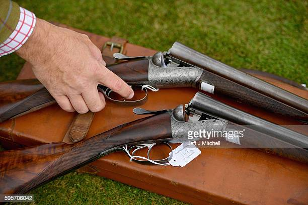 Auctioneer Gavin Gardiner holds a pair of 12bore round action ejector guns made byJohn Dickson Sonsat Gleneagles Hotel on August 26 2016 in...