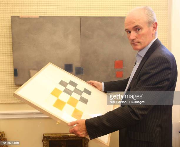 Auctioneer James O'Halloran of Adams in Dublin holds a work by Sean Skully with another by Felim Egan in the background as he prepares for an auction...