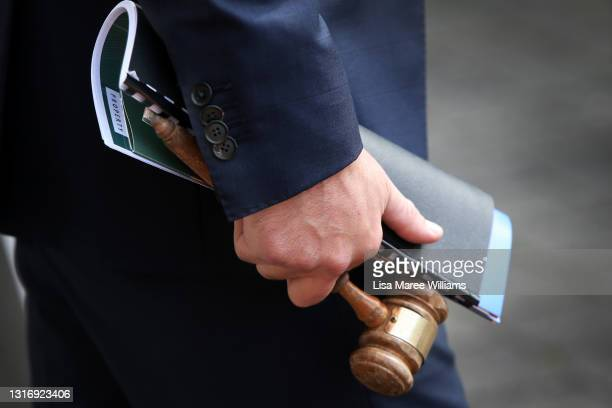 Auctioneer Jesse Davidson holds a gavel during an auction of a residential property in the suburb of Strathfield on May 08, 2021 in Sydney,...