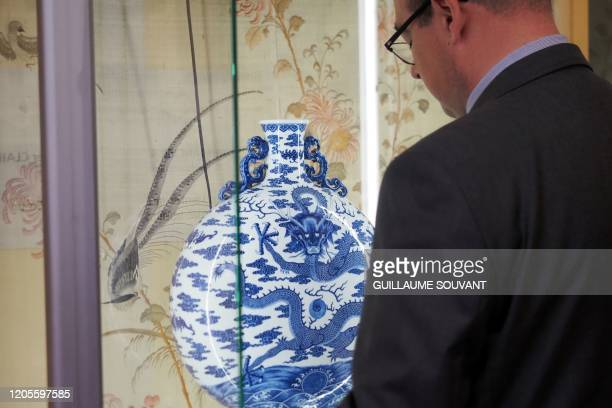Auctioneer Olivier Clair stands in front of a rare blue white and celadon porcelain moon flask with a dragon which belonged to the 18th century's...