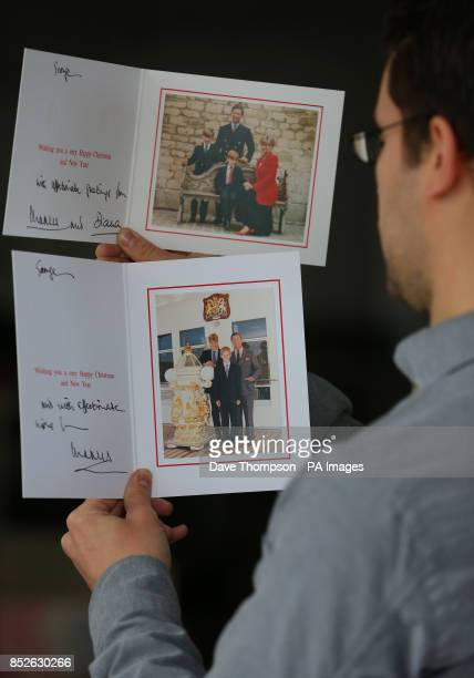 Auctioneer Paul Fairweather holds Christmas cards from 1991 and 1997 showing the Prince of Wales and Diana Princess of Wales alongside their children...