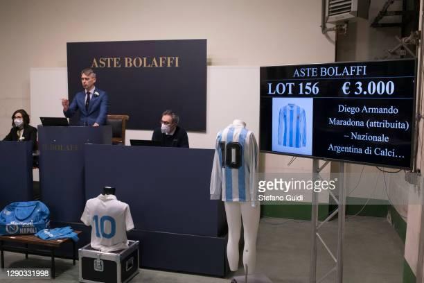 "Auctioneer sells a Diego Armando Maradona shirt during the ""Sport Memorabilia"" auction on December 09, 2020 in Turin, Italy. ""Sport Memorabilia"" is..."