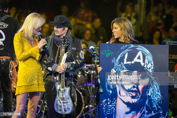 Auctiontainer Letitia Frye and musician Johnny Depp auction one of Johnny's guitars for charity at Celebrity Theatre on December 08 2018 in Phoenix...
