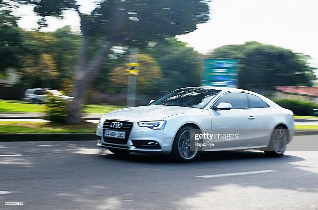 Audi A4 travelling on suburban main road. : Stock Photo